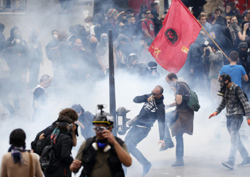 Tear gas fills the air as demonstrators clash with French riot police during a march near the Place de la Republique square in Paris